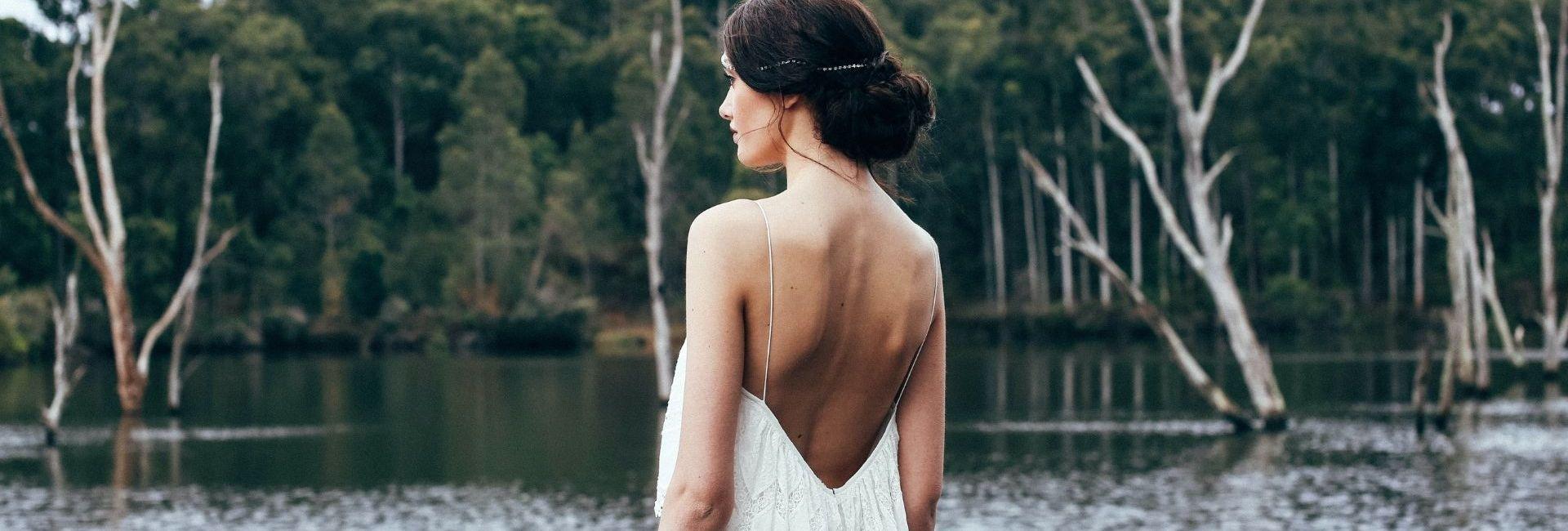 Une femme en robe de mariée dos-nu se tient devant une étendue d'eau
