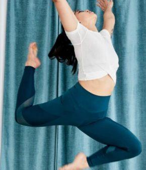 Femme sautant dans les airs dans un studio de yoga