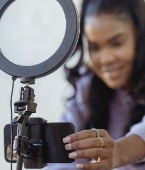 Une femme se filme au smartphone avec une ringlight telle une influenceuse