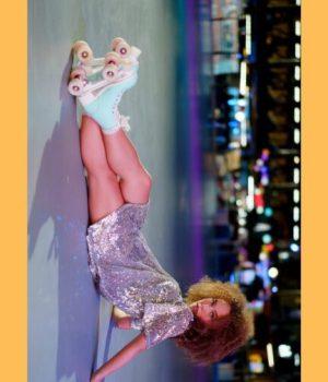 Une femme en patins à roulette et robe à sequins assise au sol