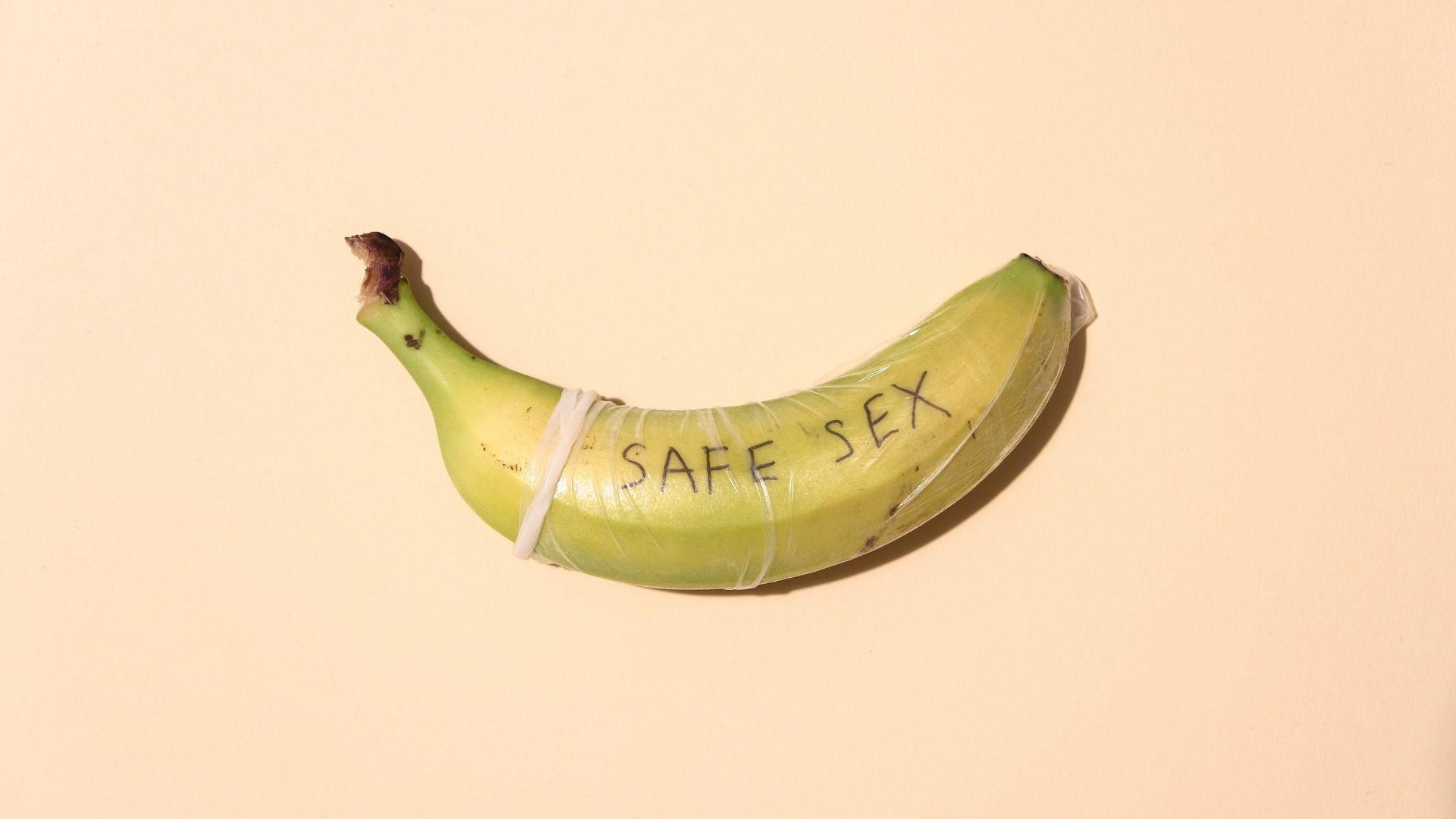 Banane entourée d'un préservatif masculin avec inscription