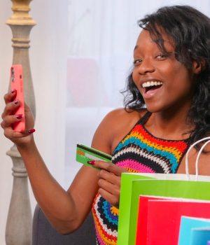 Une femme souriante tient son smartphone et sa carte bancaire.