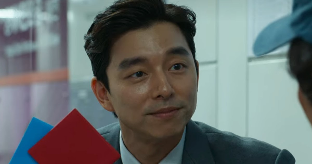 L'acteur Gong Yoo tient une carte bleue et une carte rouge pour jouer à un jeu de hasard dans la série Squid Game.