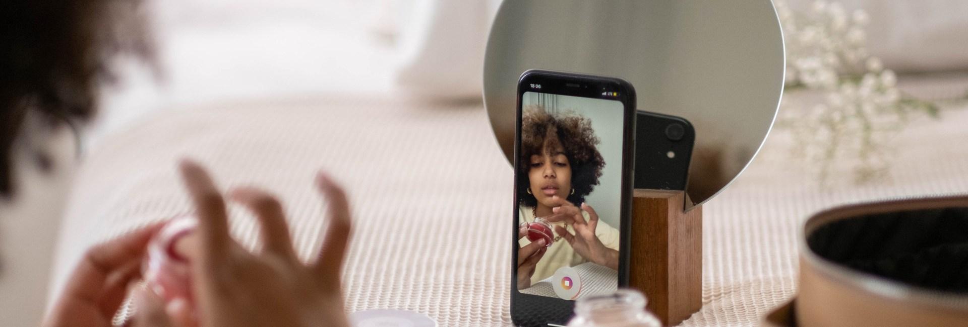 Une jeune femme qui se maquille tout en se filmant avec son téléphone