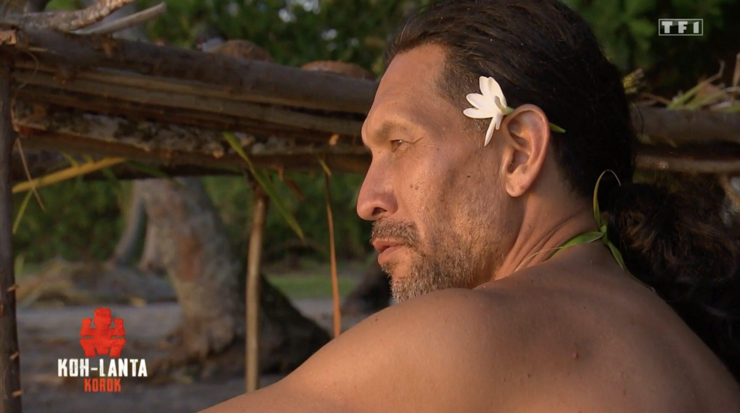 Teheiura est assis sur la plage, une fleur dans les cheveux.